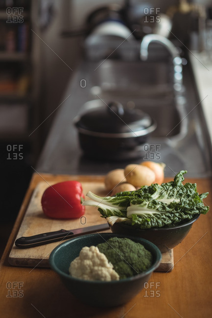 Potatoes, onion, lettuce with broccoli on cutting board in kitchen worktop