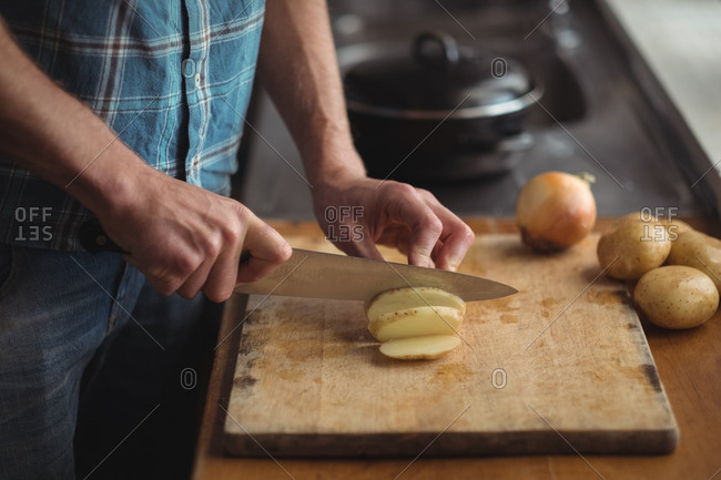 Mid section of man cutting tomatoes on cutting board in kitchen
