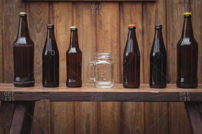 Homemade beer bottles and beer mug in a home brewery