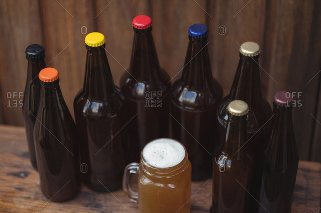 Homemade beer bottles and a mug of beer in a home brewery