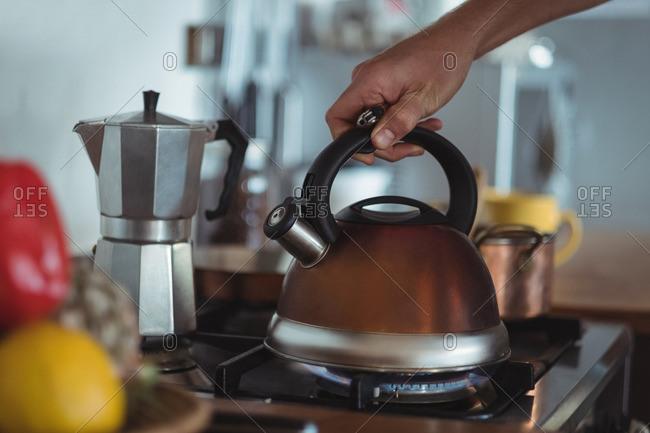 Preparing tea in teakettle on stove in kitchen