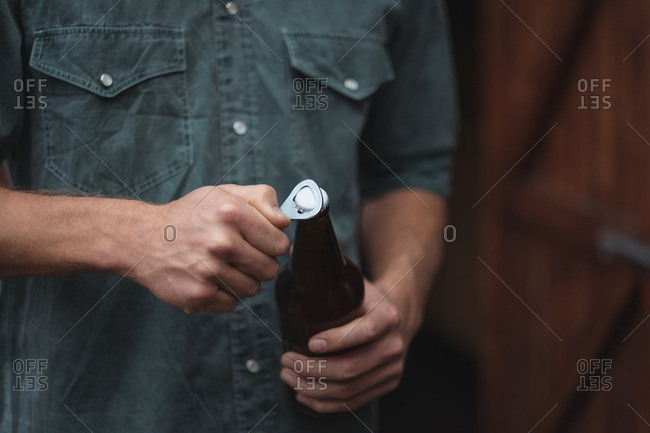 Close-up of man opening a beer bottle