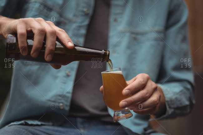 Close-up of man pouring beer into a beer glass