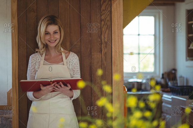Portrait of beautiful woman holding recipe book