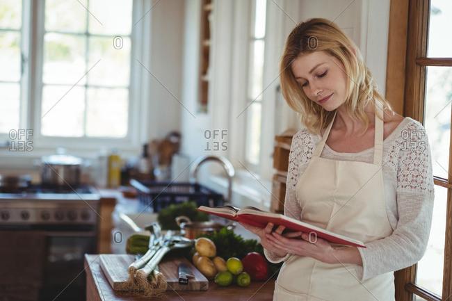 Beautiful woman reading recipe book in kitchen