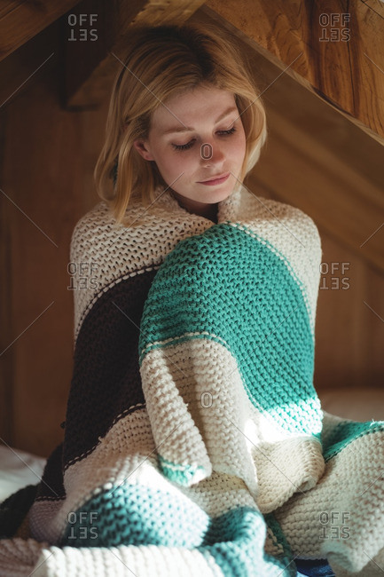 Beautiful woman wrapped in woolen blanket in bedroom