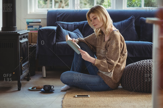 Beautiful woman reading book while having tea in living room