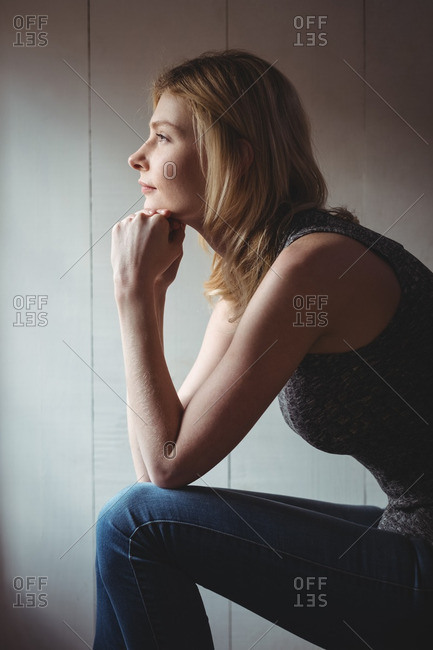 Thoughtful woman sitting with hand on chin