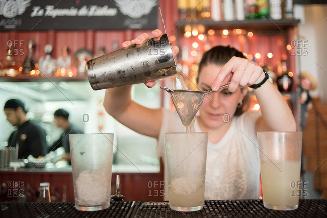 April 20, 2016: Bartender pouring a cocktail through a sieve at a Mexican restaurant