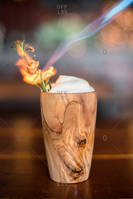 Cocktail with whipped cream and flaming rosemary in a wooden cup