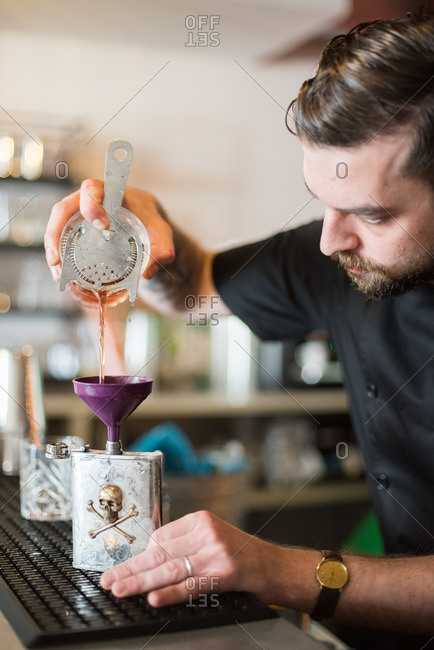 April 20, 2016: Bartender pouring a drink into a flask at a Mexican restaurant