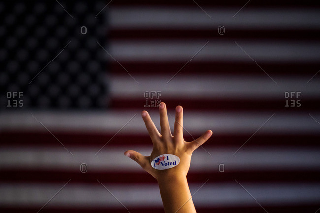 "Child's hand with an ""I Voted"" sticker in front of an American flag"