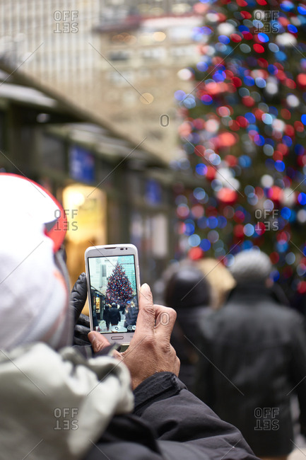 Man taking a photo of a Christmas tree with red, white and blue lights
