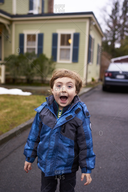 Boy in a jacket standing in a driveway yelling