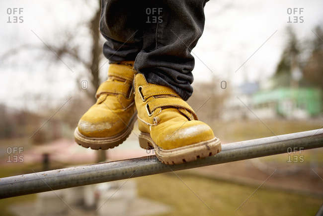 Boots of a boy on a bar at a playground