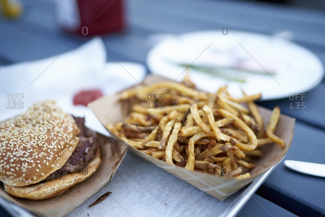 Burger and fries in cardboard containers on a picnic table