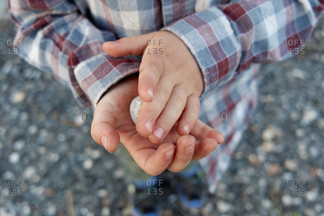 Boy in a plaid shirt holding a stone in his hands