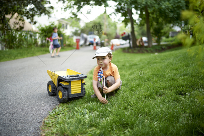 Boy playing with a pinwheel and toy dump truck