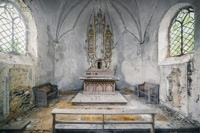 Pews and an altar in a deteriorating chapel