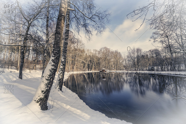 Sky reflected in a pond surrounded by snow