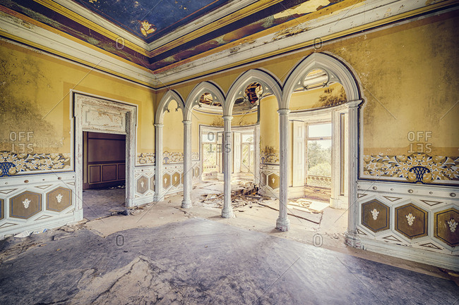 Interior room of an abandoned castle with archways and columns