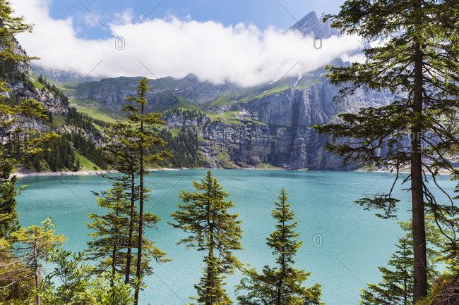 Bright blue lake surrounded by trees and mountains