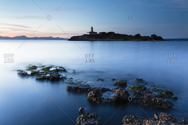 Distant lighthouse at sunrise on the island of Illa d'Alcanada, Spain