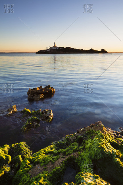 Lighthouse on the island of Illa d'Alcanada, Spain at sunrise in the distance
