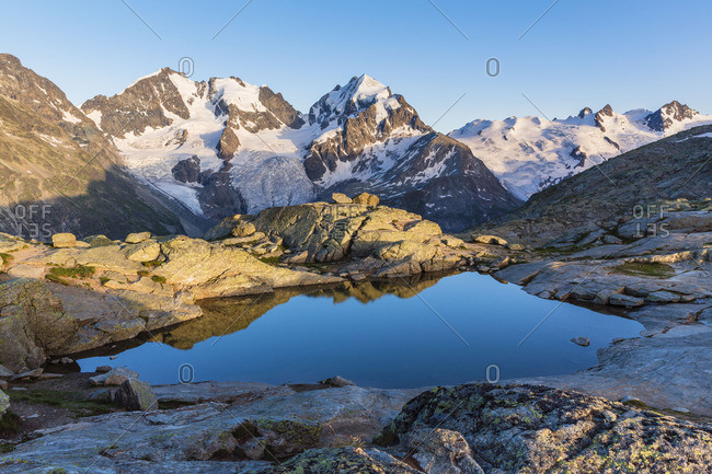 Pool of water surrounded by snow-capped mountains at sunrise