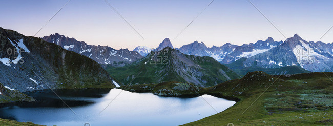 Round lake surrounded by snow-capped mountains at sunset