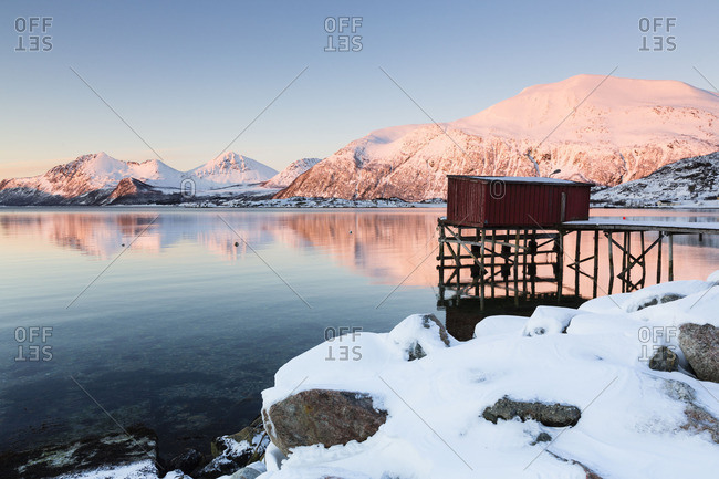 Waterfowl shelter on the edge of a snowy lake