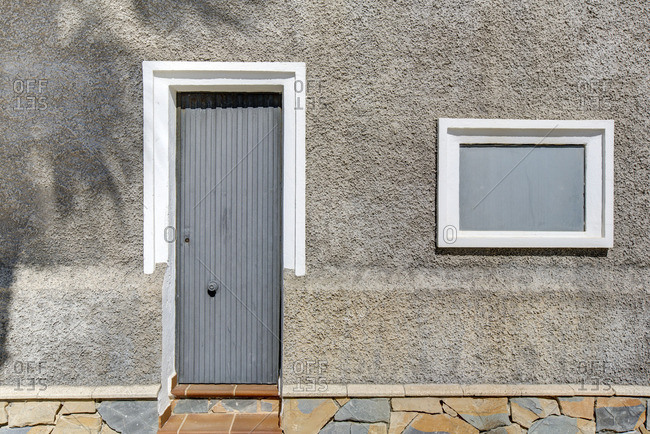 Door and window on the front of a gray stucco house