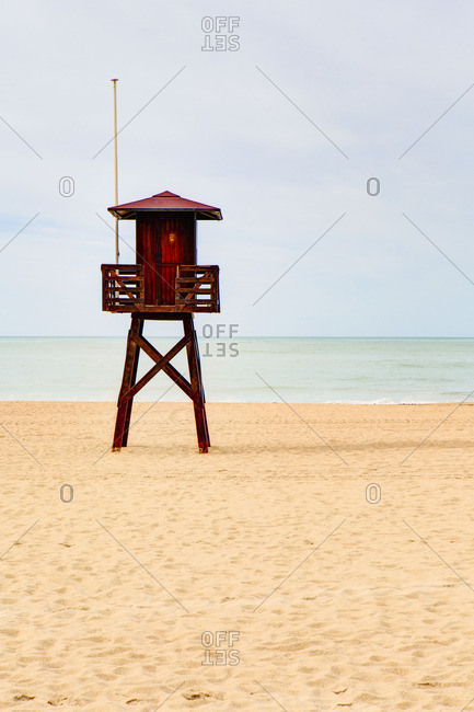 Red wooden lifeguard tower on a beach