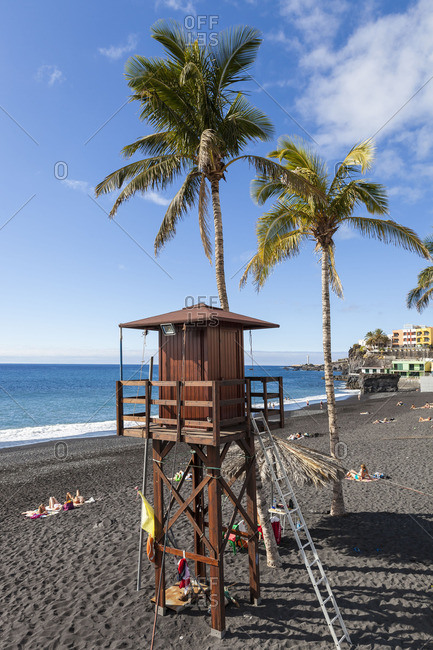 Lifeguard stand and palm trees on a black sand beach