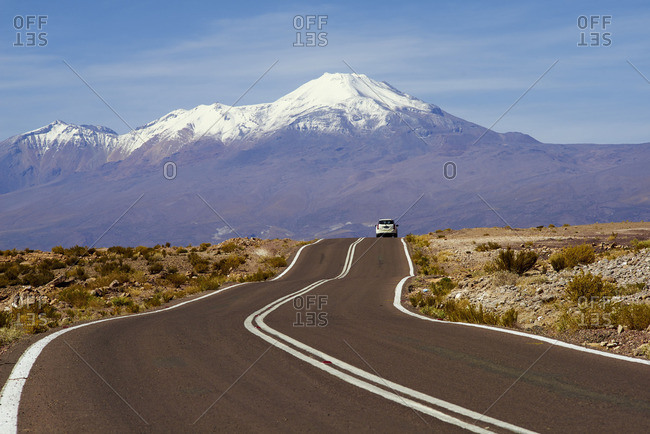 Car on a winding road with a snow-capped volcanic mountain in the distance