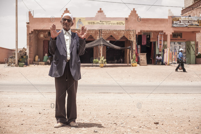 Ouarzazate, Morocco - June 7, 2016: Senior man standing on a street with his hands held up