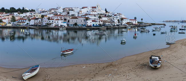 Ferragudo, Portuga - June 7, 2016l: Fishing boats on the Rio Arade in front of the village at dusk