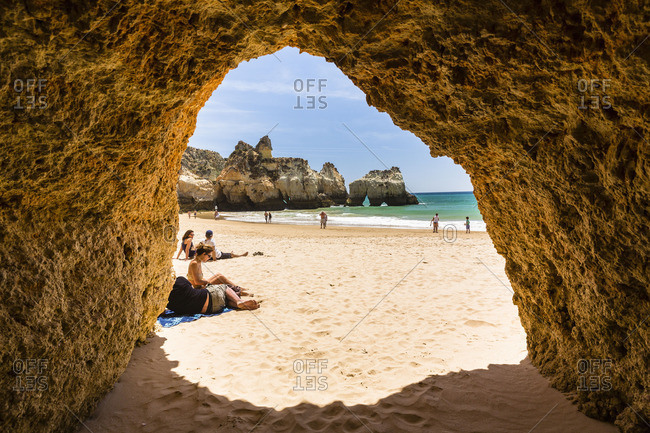 Portimao, Portugal - June 7, 2016: View through a rock arch of beachgoers at Praia dos Tres Irmaos