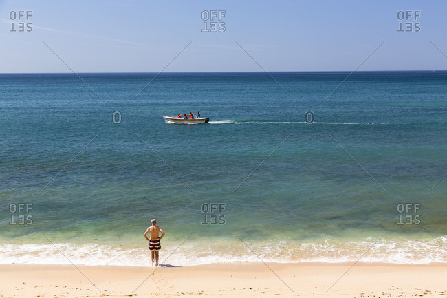 Lagoa, Portugal - June 7, 2016: Man standing on the beach watching a passing motor boat at Praia da Marinha