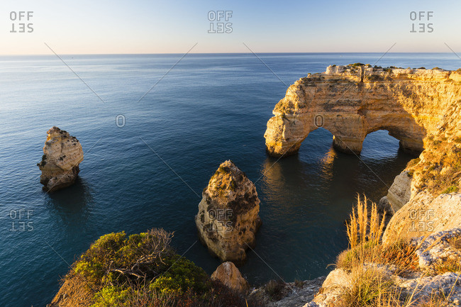 Double arch rock formation along the coastline at Praia da Marinha, Lagoa, Portugal