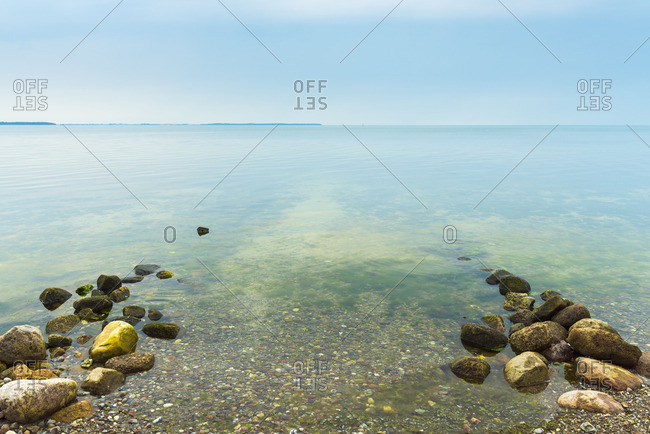 Calm shallow sea at a pebble beach in Vordingborg, Denmark