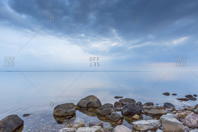 Stone beach and calm, still sea surface at Kerteminde, Denmark