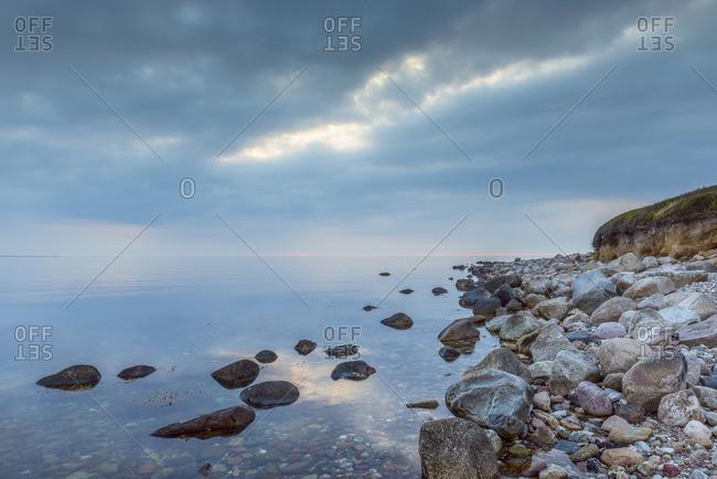 Stone beach coastline and calm, still sea at Kerteminde, Denmark