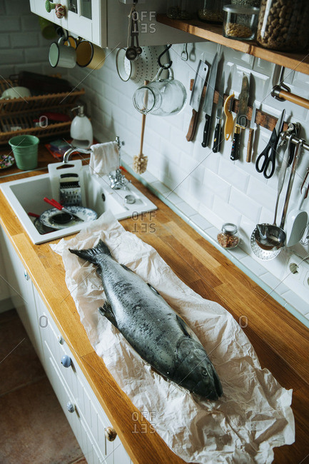 Raw fish on paper on a wooden counter