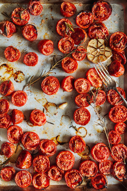Overhead view of roasted tomatoes with herbs on a baking pan