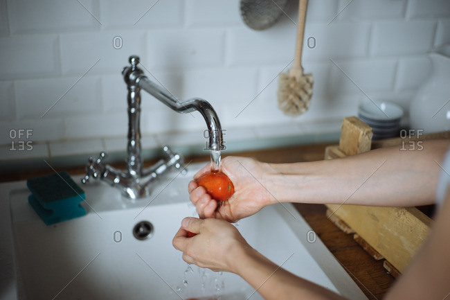 Woman in a kitchen rinsing off a tomato