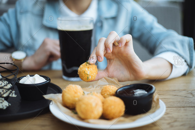 Woman eating cheese balls and drinking dark beer