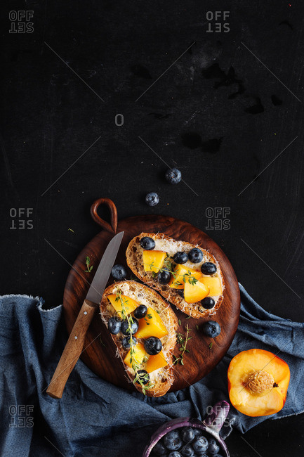 Toast topped with cheese and fruit on a slate counter