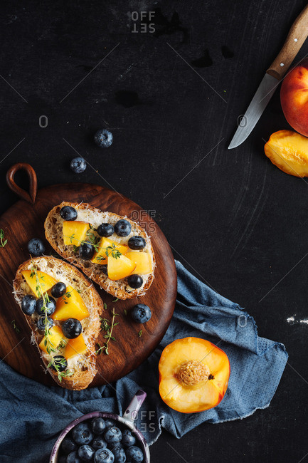 Fruit topped toast on a slate counter
