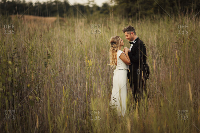 Bridal couple embracing in tall grass